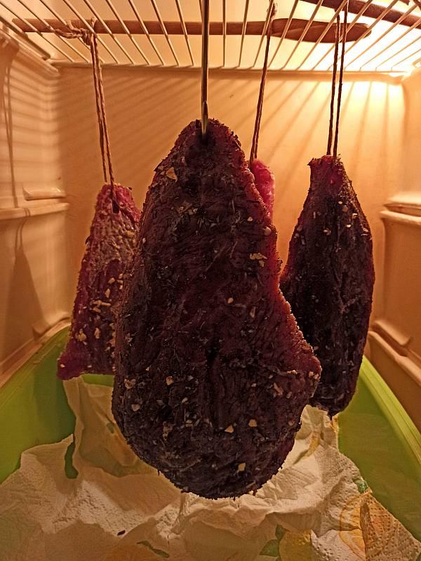 Schinken hängen zum Pökeln in einem Kühlschrank.